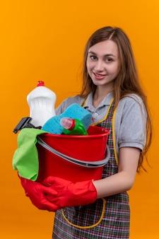 Giovane bella ragazza in grembiule e guanti di gomma che tengono secchio con strumenti di pulizia che guarda l'obbiettivo sorridente posotove e felice