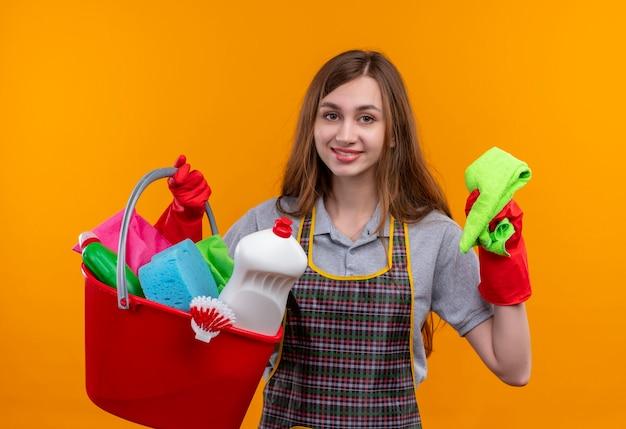 Giovane bella ragazza in grembiule e guanti di gomma che tiene secchio con strumenti di pulizia e tappeto sorridendo allegramente guardando la telecamera, pronta per la pulizia