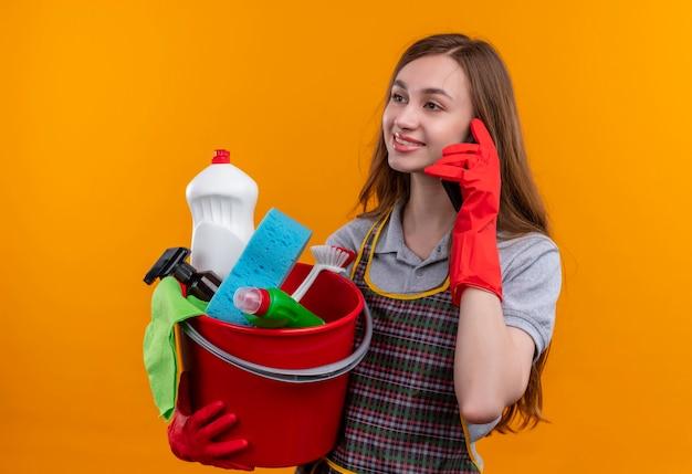 Giovane bella ragazza in grembiule e guanti di gomma che tengono secchio con strumenti di pulizia sorridente mentre parla al telefono cellulare