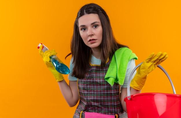 Giovane bella ragazza in grembiule e guanti di gomma che tengono spray per la pulizia e secchio che sembrano confusi e molto ansiosi