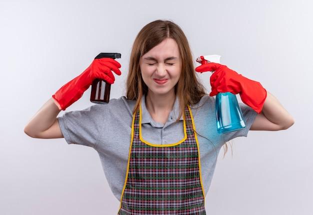 Giovane bella ragazza in grembiule e guanti di gomma che tengono spray per la pulizia vicino alle tempie con espressione infastidita sul viso
