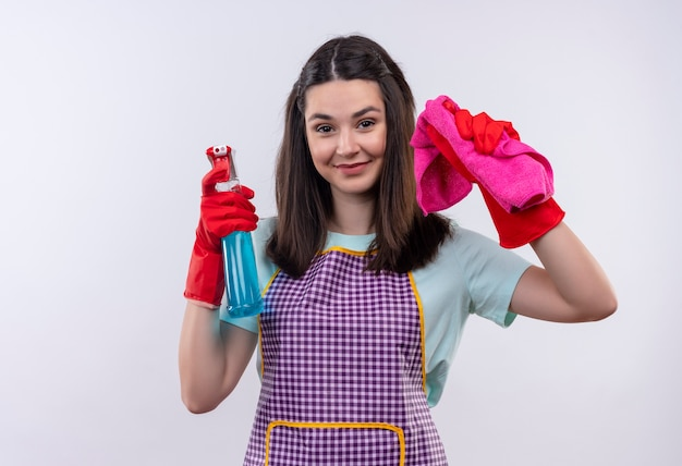 Young beautiful girl in apron and rubber gloves holding cleaning spray and rug looking at camera smiling cheerfully, ready for cleaning