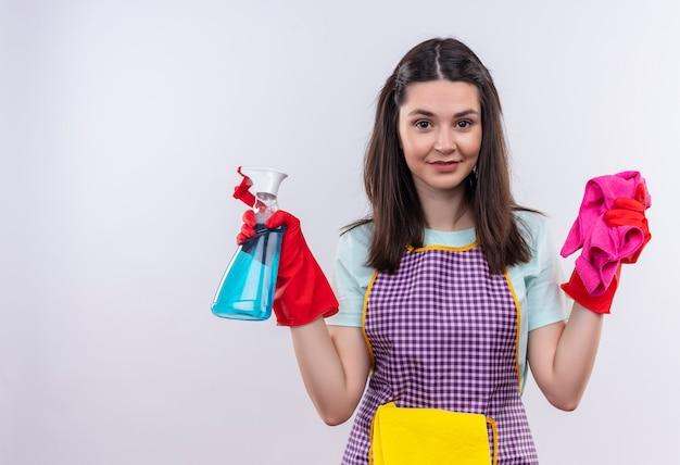 Giovane bella ragazza in grembiule e guanti di gomma che tengono spray per la pulizia e tappeto che guarda l'obbiettivo sorridente fiducioso, pronto per la pulizia