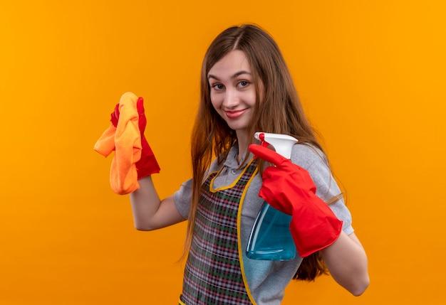 Giovane bella ragazza in grembiule e guanti di gomma che tengono spray per la pulizia e tappeto guardando la telecamera sorridente positivo e felice, pronto per la pulizia