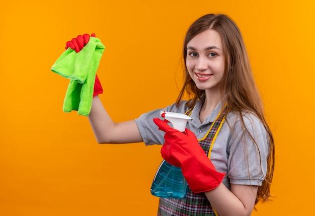 Giovane bella ragazza in grembiule e guanti di gomma che tengono spray per la pulizia e tappeto che guarda l'obbiettivo sorridente, pronto per la pulizia