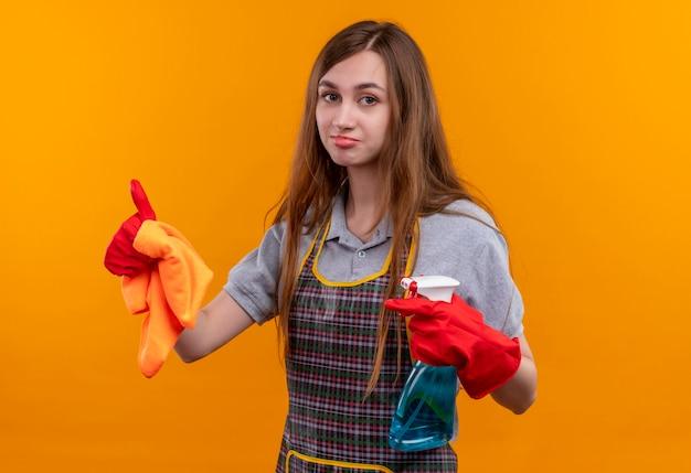 Giovane bella ragazza in grembiule e guanti di gomma che tiene spray per la pulizia e tappeto che guarda l'obbiettivo con sorriso scettico sul viso, mostrando i pollici in su