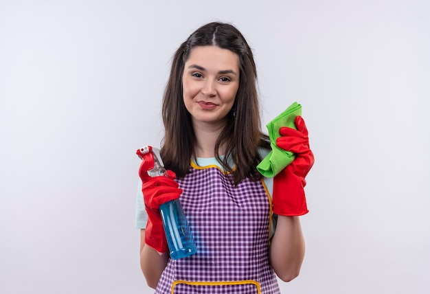 Young beautiful girl in apron and rubber gloves holding cleaning spray and rug smiling confident, ready for cleaning