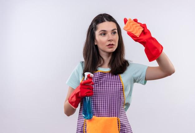 Giovane bella ragazza in grembiule e guanti di gomma che tengono spray per la pulizia e spugna andando a pulire guardando fiducioso