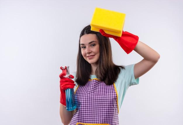 Giovane bella ragazza in grembiule e guanti di gomma che tengono spray per la pulizia e spugna che guarda l'obbiettivo sorridente fiducioso, pronto per la pulizia