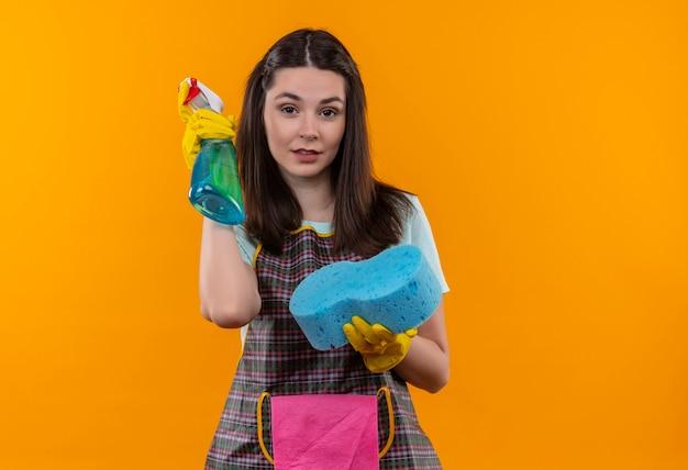 Giovane bella ragazza in grembiule e guanti di gomma che tengono spray per la pulizia e spugna che guarda l'obbiettivo sorridente fiducioso