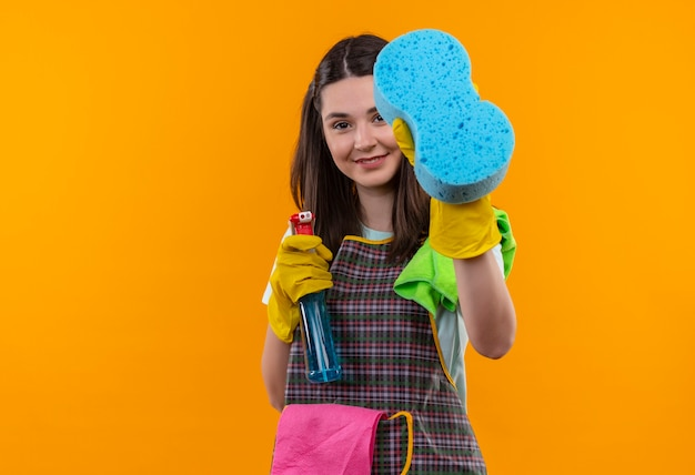 Young beautiful girl in apron and rubber gloves holding cleaning spray and sponge looking at camera smiling with happy face, ready for cleaning