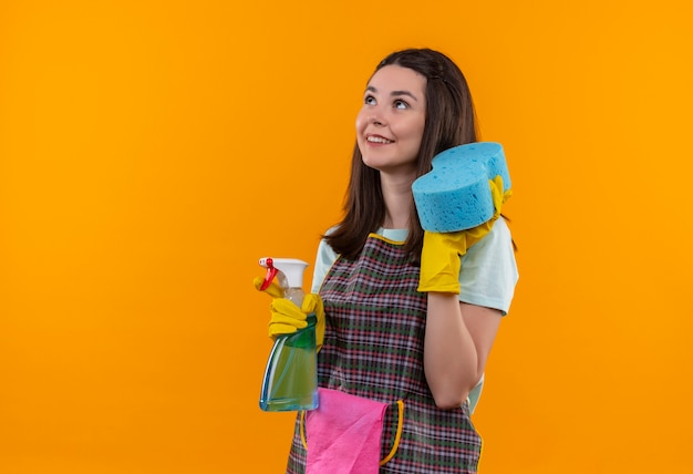 Young beautiful girl in apron and rubber gloves holding cleaning spray and sponge looking up smiling confident