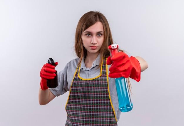 Giovane bella ragazza in grembiule e guanti di gomma che tengono spray per la pulizia mirando con loro con la faccia seria