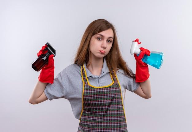 Giovane bella ragazza in grembiule e guanti di gomma che tengono gli spray per la pulizia in mani alzate che sembrano confusi e molto ansiosi