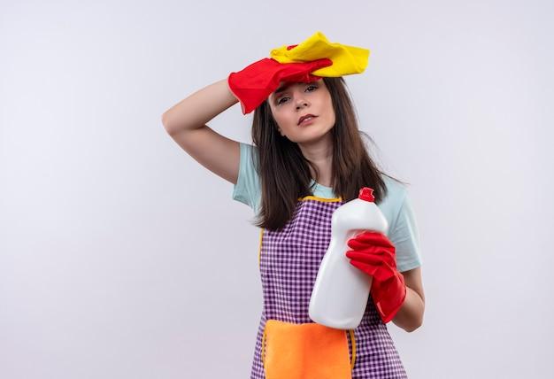 Giovane bella ragazza in grembiule e guanti di gomma che tengono i rifornimenti di pulizia e testa commovente stanca e oberata di lavoro rud
