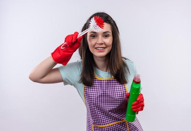 Giovane bella ragazza in grembiule e guanti di gomma che tengono i prodotti per la pulizia e la spazzola che guarda lontano con la mano sopra la testa per guardare qualcosa