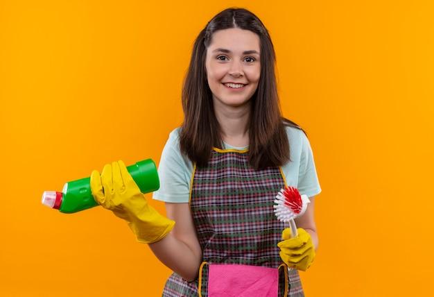 Giovane bella ragazza in grembiule e guanti di gomma che tengono i prodotti per la pulizia e spazzolatura sorridente fiducioso