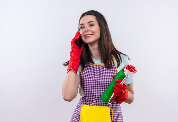 Giovane bella ragazza in grembiule e guanti di gomma che tengono i prodotti per la pulizia e spazzolatura sorridente mentre parla al telefono cellulare