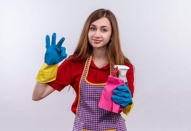 Giovane bella ragazza in grembiule e guanti di gomma che tengono i rifornimenti di pulizia che sorridono facendo segno giusto
