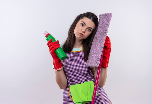 Young beautiful girl in apron and rubber gloves holding cleaning suppliesand mop looking tired and overworked with sad expression on face