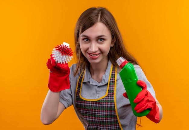 Giovane bella ragazza in grembiule e guanti di gomma che tengono i prodotti per la pulizia della holding e spazzola per strofinare sorridendo allegramente guardando la telecamera sornione