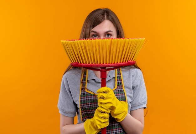 Young beautiful girl in apron and rubber gloves holding mop hading face behind it peeking over