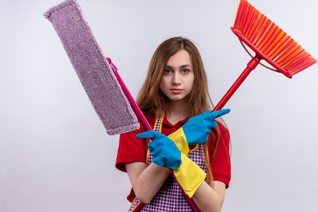 Giovane bella ragazza in grembiule e guanti di gomma che tengono mops attraversando le mani che guarda l'obbiettivo con la faccia seria