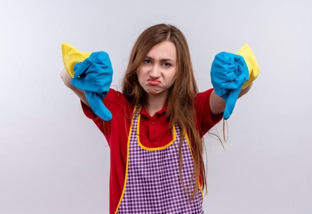 Giovane bella ragazza in grembiule e guanti di gomma che guarda l'obbiettivo scontento che mostra i pollici verso il basso con entrambe le mani