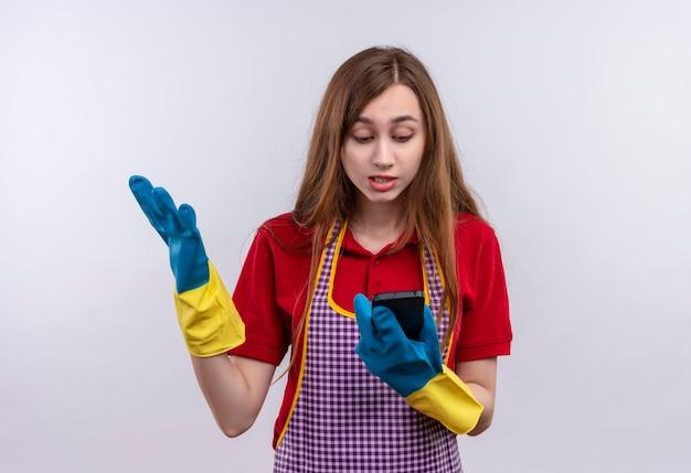 Giovane bella ragazza in grembiule e guanti di gomma guardando lo schermo del suo cellulare confuso