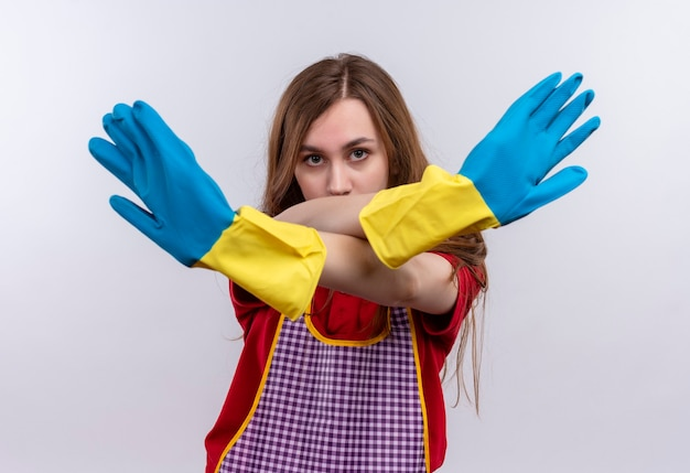 Young beautiful girl in apron and rubber gloves making defense stop gesture crossing hands