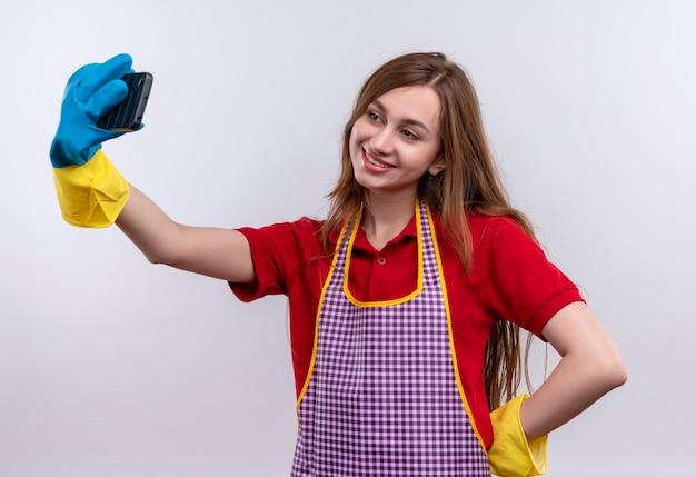 Giovane bella ragazza in grembiule e guanti di gomma prendendo selfie utilizzando il suo smartphone sorridente