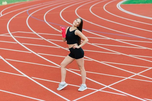 スポーツウェアの若くて美しい女の子のアスリートは、スタジアムでストレッチしながらトレーニングとランニングをしています