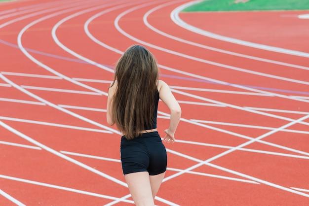 スポーツウェアの若い、美しい女の子のアスリートはトレーニングとランニング