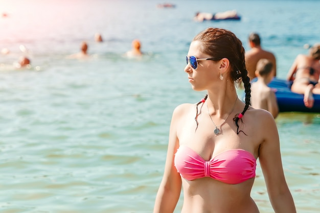 Young, beautiful girl in a bathing suit and sunglasses stands on the  of the sea. the  of vacation, vacation, summer, vacation, travel. copyspace.