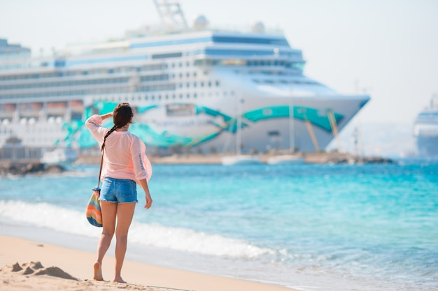 Young beautiful girl on the beach onbig cruise ship.