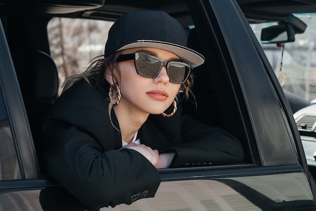 A young beautiful girl in a black car looks out of the window. a stylish girl in glasses and a cap rides in a car, leaning out of the window.