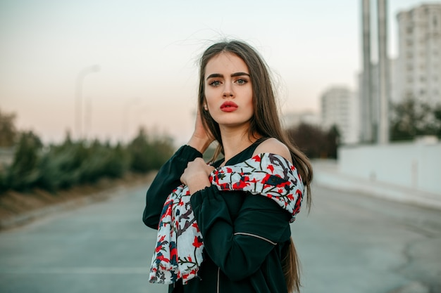 Young beautiful girl in a black jacket with a scarf posing in the evening on the street.
