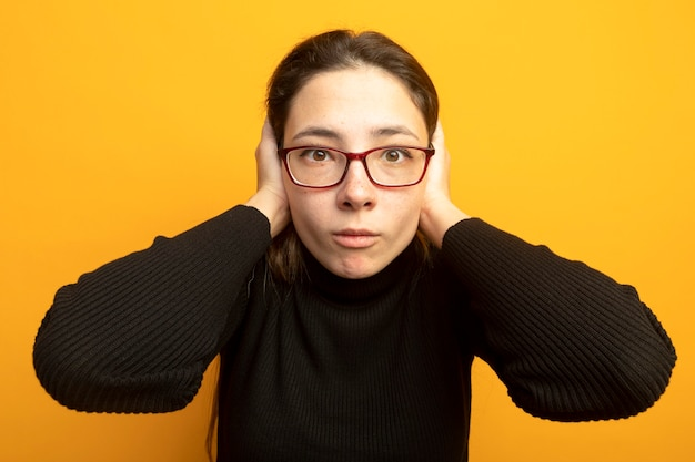 Young beautiful girl in a black turtleneck and glasses being confused and worried with hands on her head
