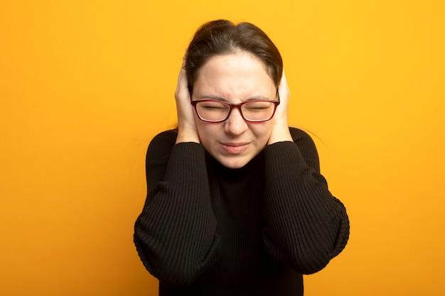 Giovane bella ragazza in un dolcevita nero e occhiali chiudendo le orecchie con le mani con espressione infastidita