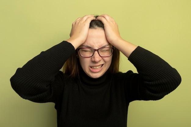 Giovane bella ragazza in un dolcevita nero e occhiali che si scatenano tenendosi per mano sulla sua testa