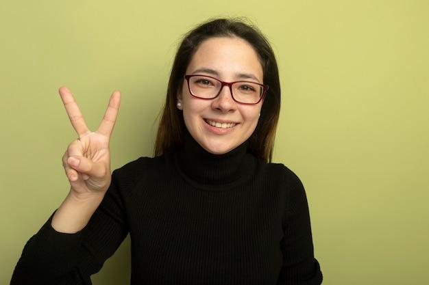 Giovane bella ragazza in un dolcevita nero e occhiali felice e positivo che mostra v-segno