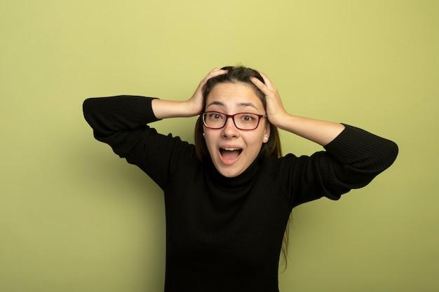 Giovane bella ragazza in un dolcevita nero e occhiali felici e sorpresi con le mani sulla sua testa