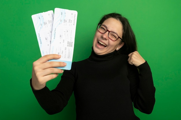 Young beautiful girl in a black turtleneck and glasses holding air tickets happy and excited clenching fist