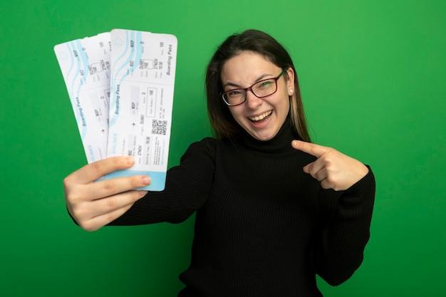 Giovane bella ragazza in un dolcevita nero e occhiali che tengono i biglietti aerei che indicano con il dito indice ai biglietti sorridenti felici