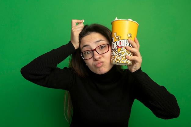 Giovane bella ragazza in un dolcevita nero e bicchieri che tengono secchio con popcorn confuso
