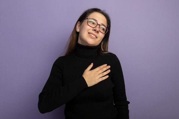 Giovane bella ragazza in un dolcevita nero e bicchieri tenendo la mano sul petto sorridente sentendosi grato