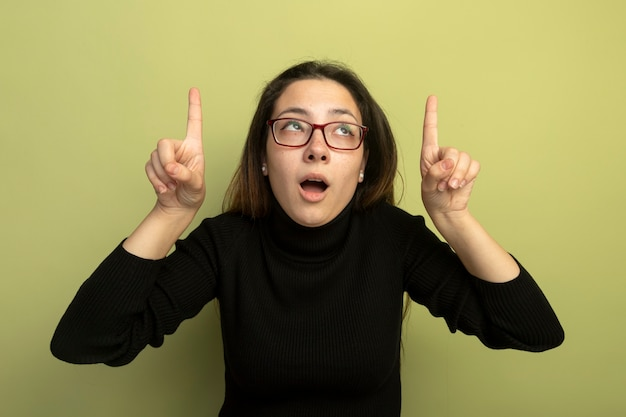 Giovane bella ragazza in un dolcevita nero e occhiali cercando pointgn con indice figners