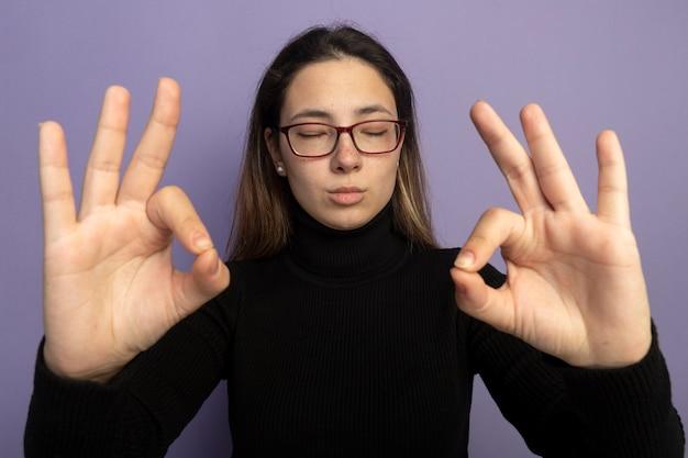 Giovane bella ragazza in un dolcevita nero e occhiali che fanno il gesto di meditazione con le dita con gli occhi chiusi