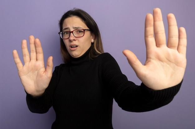 Giovane bella ragazza in un dolcevita nero e occhiali che fanno gesto di arresto tenendo la mano aperta essendo spaventato Foto Gratuite