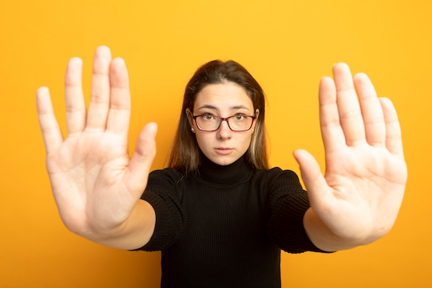 Young beautiful girl in a black turtleneck and glasses making stop sing with hands with fear expression